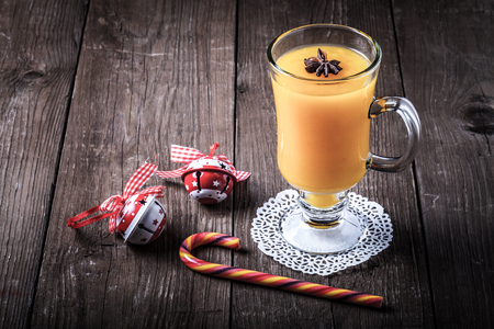 Glass of sea buckthorn beverage (kissel) on a brown wooden table or board for background. New year theme. Toned.