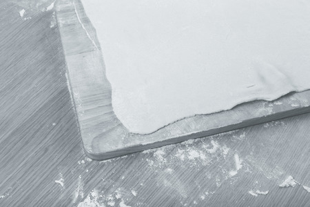 pin board: Puff dough, wooden cutting board on a light table with flour. Toned. Stock Photo