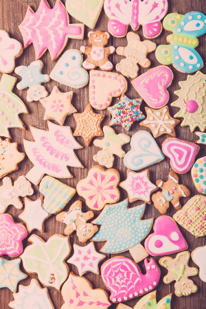 Gingerbread homemade cookies with icing colored drawings on wooden table. Toned. Standard-Bild