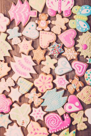 nudelholz: Lebkuchen selbst gebackenen Plätzchen mit Zuckerglasur farbigen Zeichnungen auf Holztisch. Getontes.