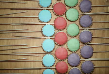 topper: Gingerbread cookies with colored mastic on sticks on the old wooden cutting board. Toned.