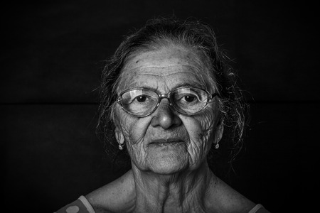 grayness: Portrait of elderly woman in a glasses. Toned.