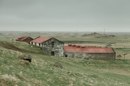 winter road: Old gray stony house on the spring landscape in the east of Iceland. Toned. Stock Photo
