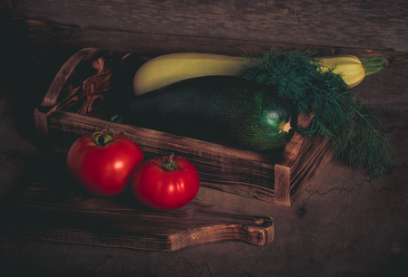front desk: Fresh vegetables on a wooden burned rustic texture for background. Rough weathered wooden board. Toned.