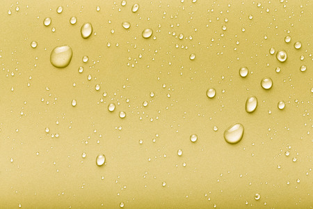 Drops of water on a color background. Yellow. Toned. Stock Photo
