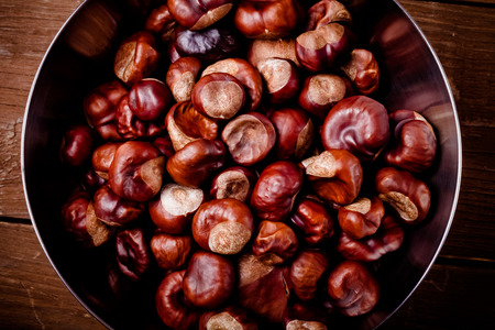 Chestnuts in a metal bowl on the old wooden background. Toned.