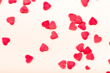 Many pink sugar hearts are scattered on a light background. Toned.