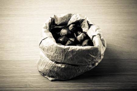 Chestnuts in a paper bag on a light wooden table. Toned.