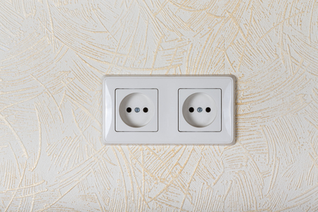 parget: Light wallpaper on a wall with electrical outlet for background. Close Up detail. Stock Photo