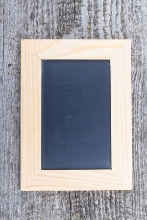 Black chalk board in a light wooden frame on the old wooden table.