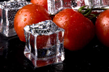 Banch of red cherry tomatos and ice cubes on black wet table. Selective focus.