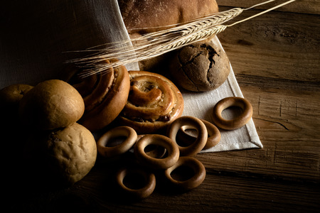 Different types of fresh bread and wheat spikes on old wooden table. Toned. Lizenzfreie Bilder