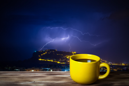 Coffee or tea in yellow cup on the wooden table opposite thunderstorm over Alanya main peninsula for background. Toned.