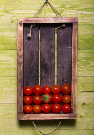 Fresh cherry tomatoes in a wooden burned rustic box on green texture for background. Rough weathered wooden board.