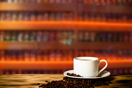Interior room: Coffee in a cup on wooden table opposite a defocused  background. Collage. Selective focus. Stock Photo