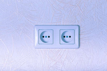 parget: Light wallpaper on a wall with electrical outlet for background. Close Up detail. Toned. Stock Photo