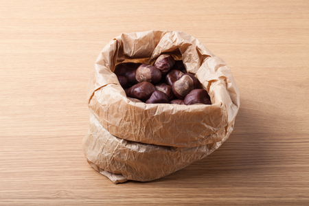 Chestnuts in a paper bag on a light wooden table. Stock Photo