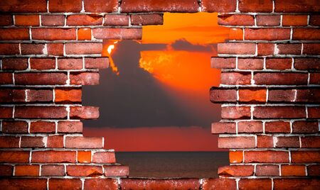 Dramatic sunset rays through a cloudy dark sky over the ocean. Landscape behind a wall of red bricks. Toned.