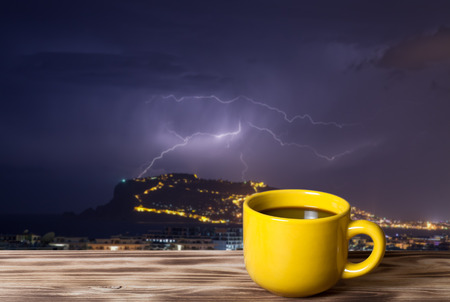 Coffee or tea in yellow cup on the wooden table opposite thunderstorm over Alanya main peninsula for background.