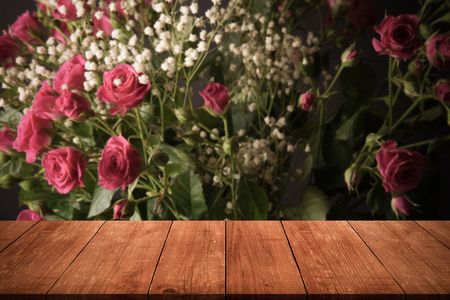 View from wooden table on wonderful bouquet of bush roses and gypsophila on a dark background Stock Photo