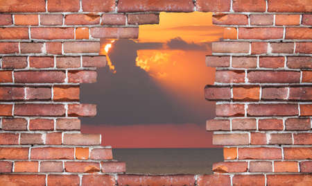 Dramatic sunset rays through a cloudy dark sky over the ocean. Landscape behind a wall of red bricks.