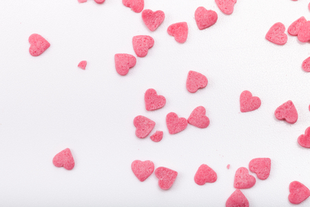 Many pink sugar hearts are scattered on a light background.