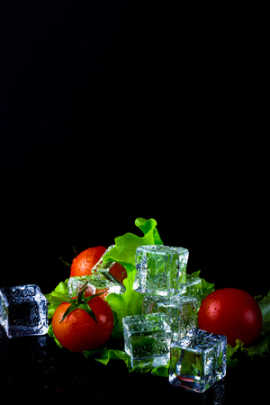 Banch of red cherry tomatos, green salad and ice cubes on black wet table. Selective focus. Toned. Stock Photo