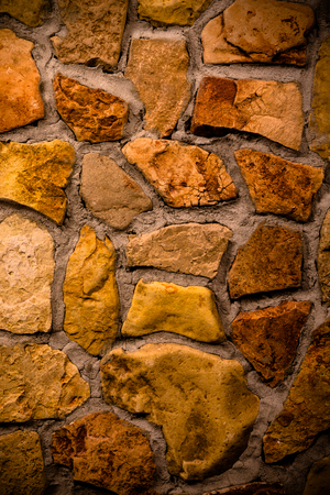 Wall built of natural stone with cement. Toned.