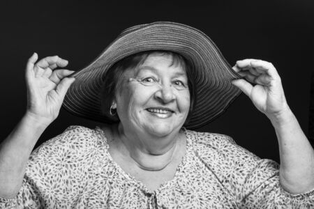 Studio portrait of elderly woman with hat. Smile. Toned.