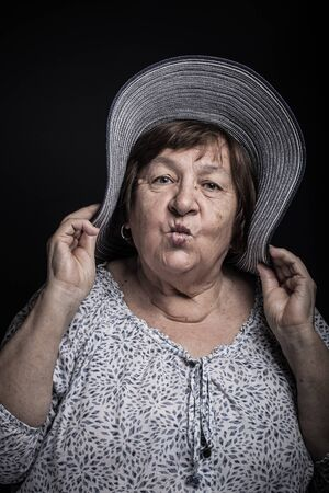 Studio portrait of elderly woman with hat. Kiss. Toned.