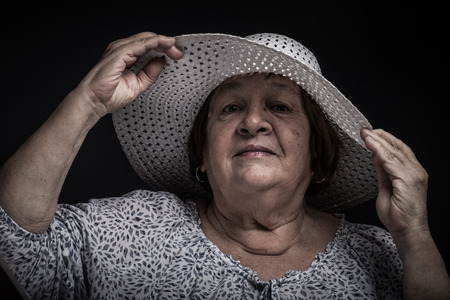 Studio portrait of elderly woman with hat. Coquetry. Toned. Stock Photo