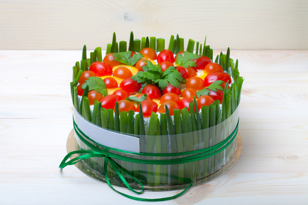 Non-sweet holiday cake with red fish, green onion, cherry tomatoes, cream cheese and parsley on light wooden background.