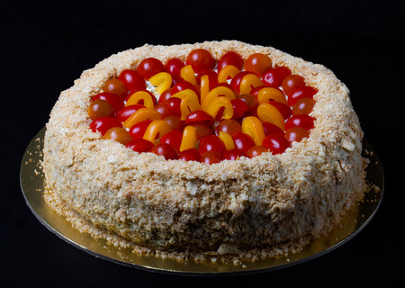 Non-sweet holiday cake with red fish, cherry tomatoes, cream cheese and yellow pepper on dark background.