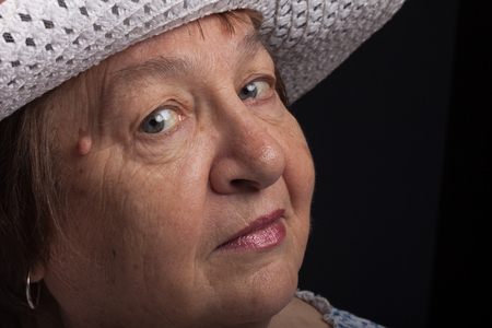 Studio portrait of elderly woman with hat. Coquetry.