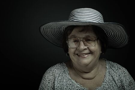 Studio portrait of elderly woman with glasses and hat. Smile. Toned. Stock Photo