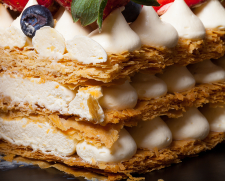Puff homemade cake with cream and berries.