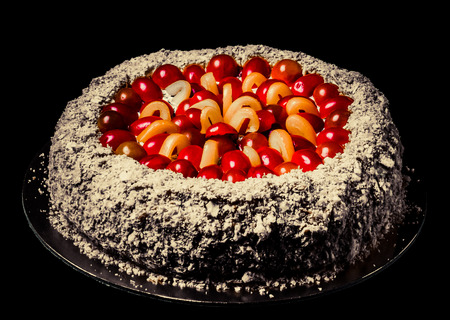 Non-sweet holiday cake with red fish, cherry tomatoes, cream cheese and yellow pepper on dark background. Toned.