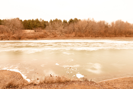 Frozen river with snow and ice in the autumn landscape. Toned.