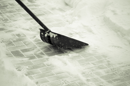 Snow shovel on a tile ground. Toned.