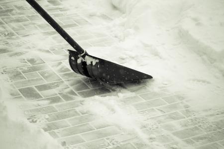 Snow shovel on a tile ground. Toned.