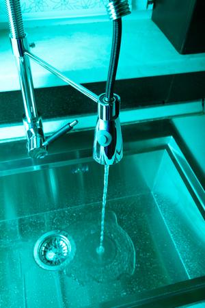 Flow of water in a metal sink on a modern kitchen. Toned. Reklamní fotografie