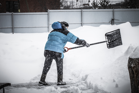 Old woman in warm blue jacket clears a snowdrifts with a snow shovel. Toned.