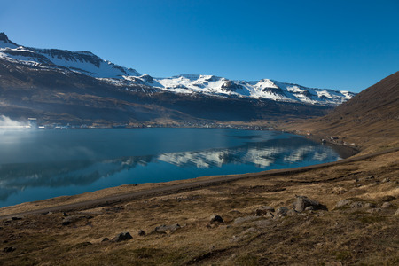 View to the small town and snowy mountains in the fjord of Iceland. Stock Photo