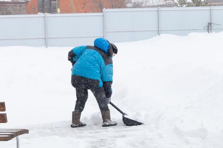 Stara kobieta w ciepłej niebieskiej kurtce odśnieża zaspy łopatą do śniegu.