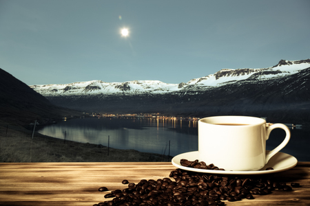 Coffee and white cup on the wooden table on the background of foggy landscape of the fjords of Iceland. Collage. Toned.