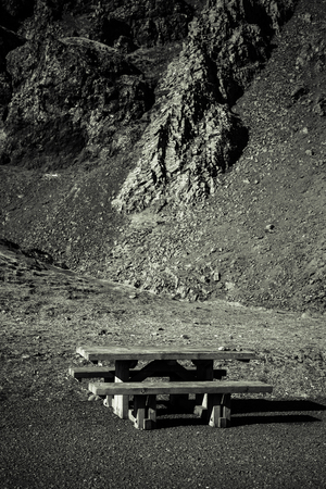 Wooden bench and table on a beautiful multicolored spring landscape of Iceland. Toned.