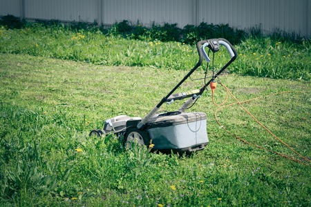 Lawn mower in the spring garden. Toned.