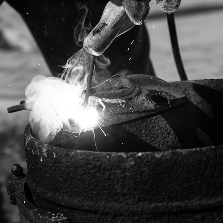 An experienced welder at work. Preparation and welding process of cast iron furnace. Selection focus. Shallow depth of field. Toned. Imagens - 124707327
