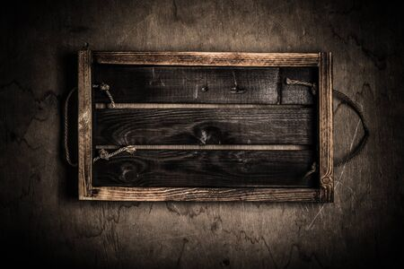 Handmade burned box on a wooden rustic texture for background. Rough weathered wooden board. Toned.