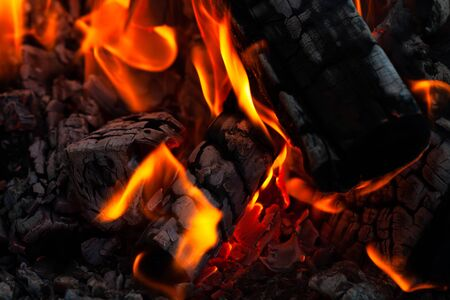 Burning wood logs, cooking on fire, warm evening, sparkles in the air, warm air from the fire Stock Photo